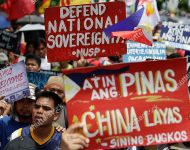 Mandatory Credit: Photo by Aaron Favila/AP/Shutterstock (10302834d) Protesters hold slogans during a rally outside the Chinese Consulate at the financial district of Makati, metropolitan Manila to mark the Independence Day on . The group said they condemn the administration of Philippine President Rodrigo Duterte for it's alleged subservience to the dictates of U.S. and China. They also demanded that China must stop its continued occupation of the disputed South China Sea because it disrespects sovereign rights Independence Day Protest, Manila, Philippines - 12 Jun 2019